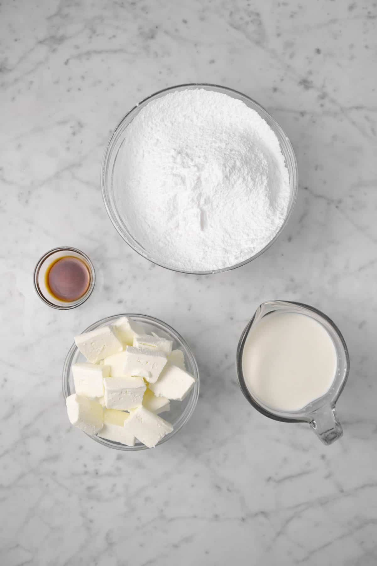 ingredients for cream cheese frosting on a marble counte