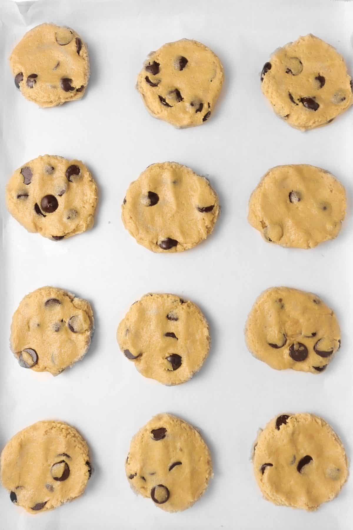 peanut butter and chocolate chip cookie dough pressed down onto a baking sheet