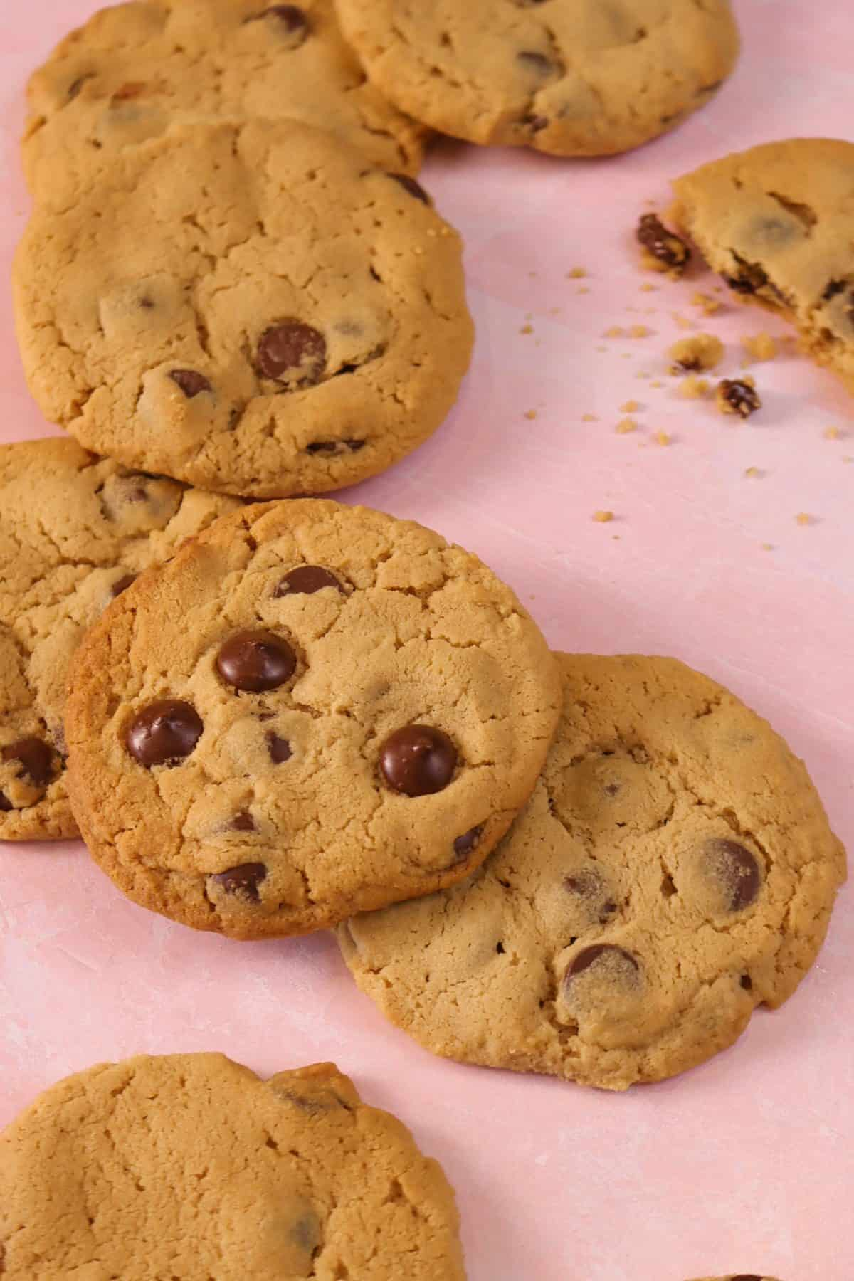 peanut butter chocolate chip cookies spread out on a pink marble board