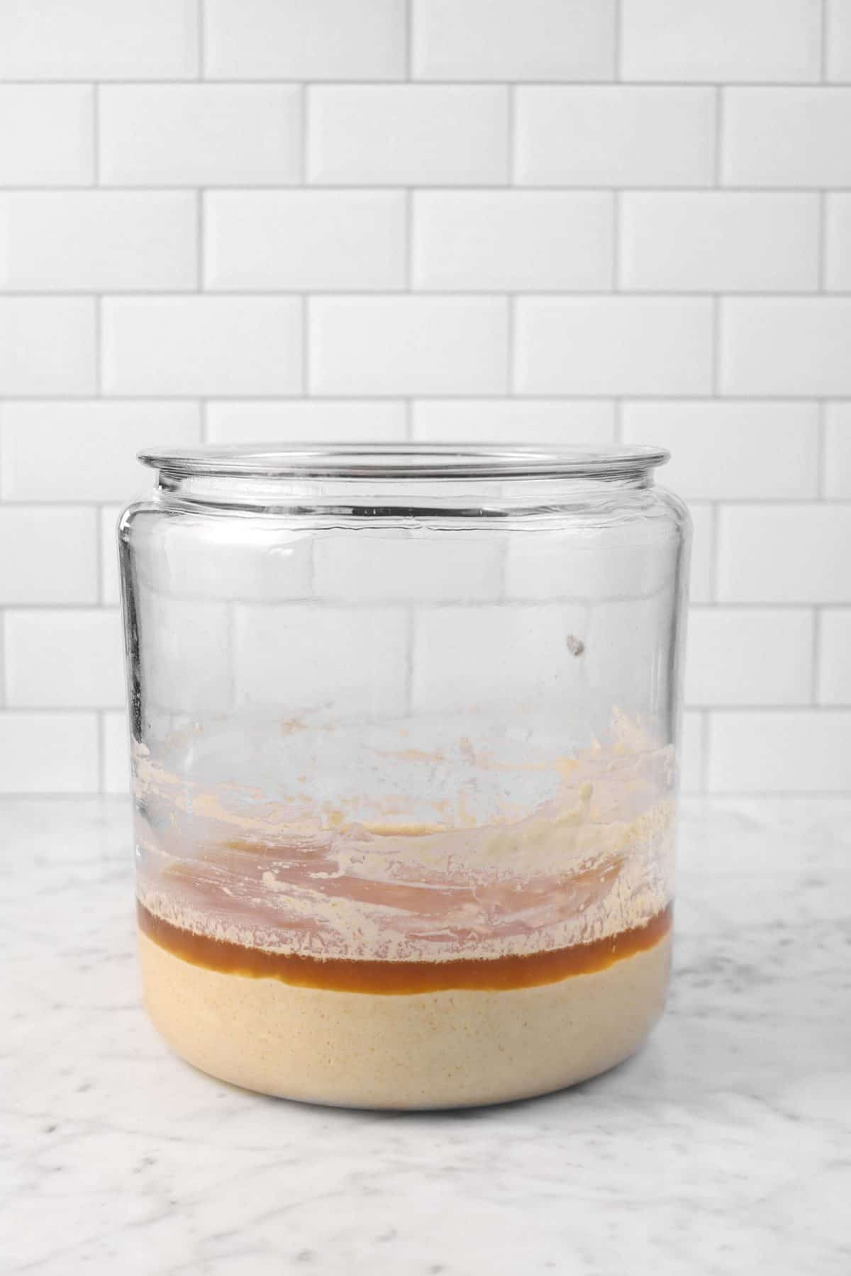 sourdough starter in a glass jar on a marble counter