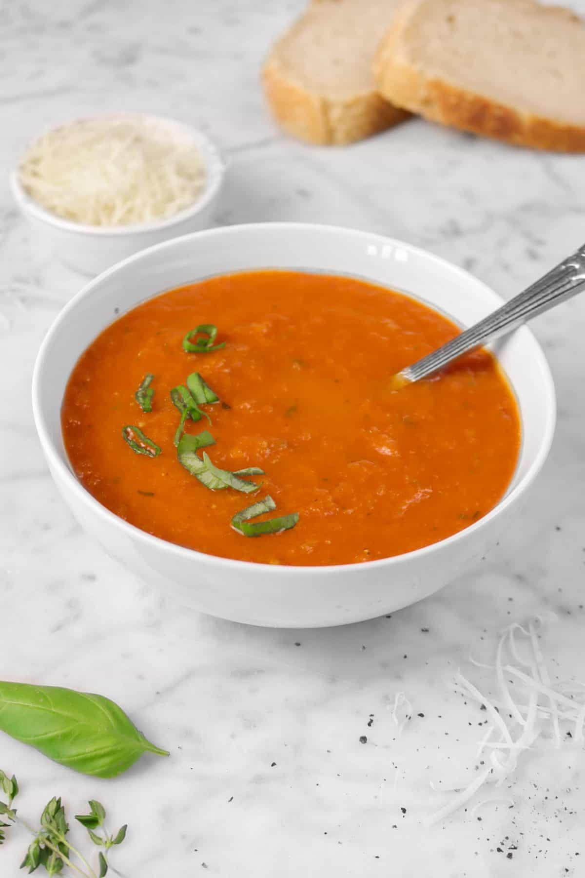 a bowl of tomato soup with a spoon on a marble counter with bread, grated cheese, and fresh herbs