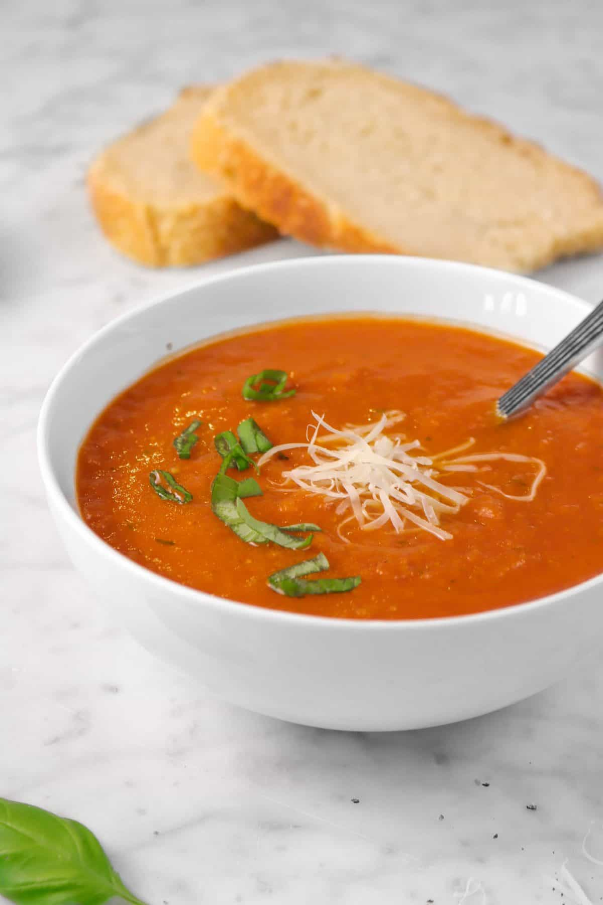 a bowl of tomato soup with cheese and sliced basil on a marble counter with slices of bread