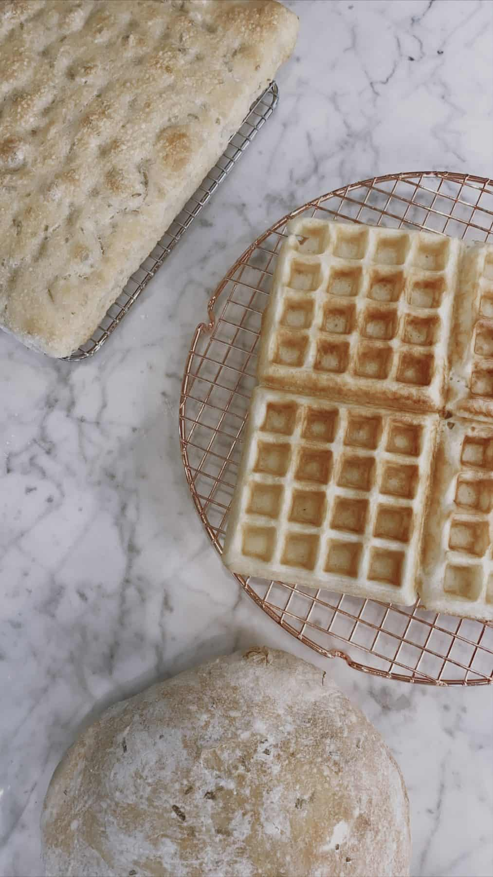 two loaves of focaccia and four sourdough waffles on a marble counter