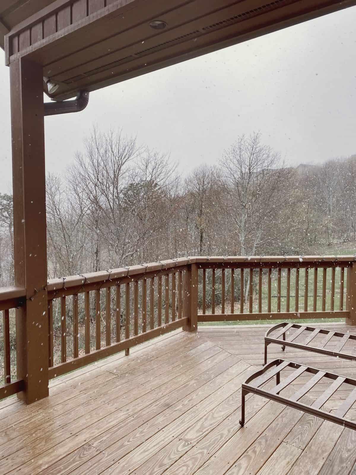 snow falling on a balcony