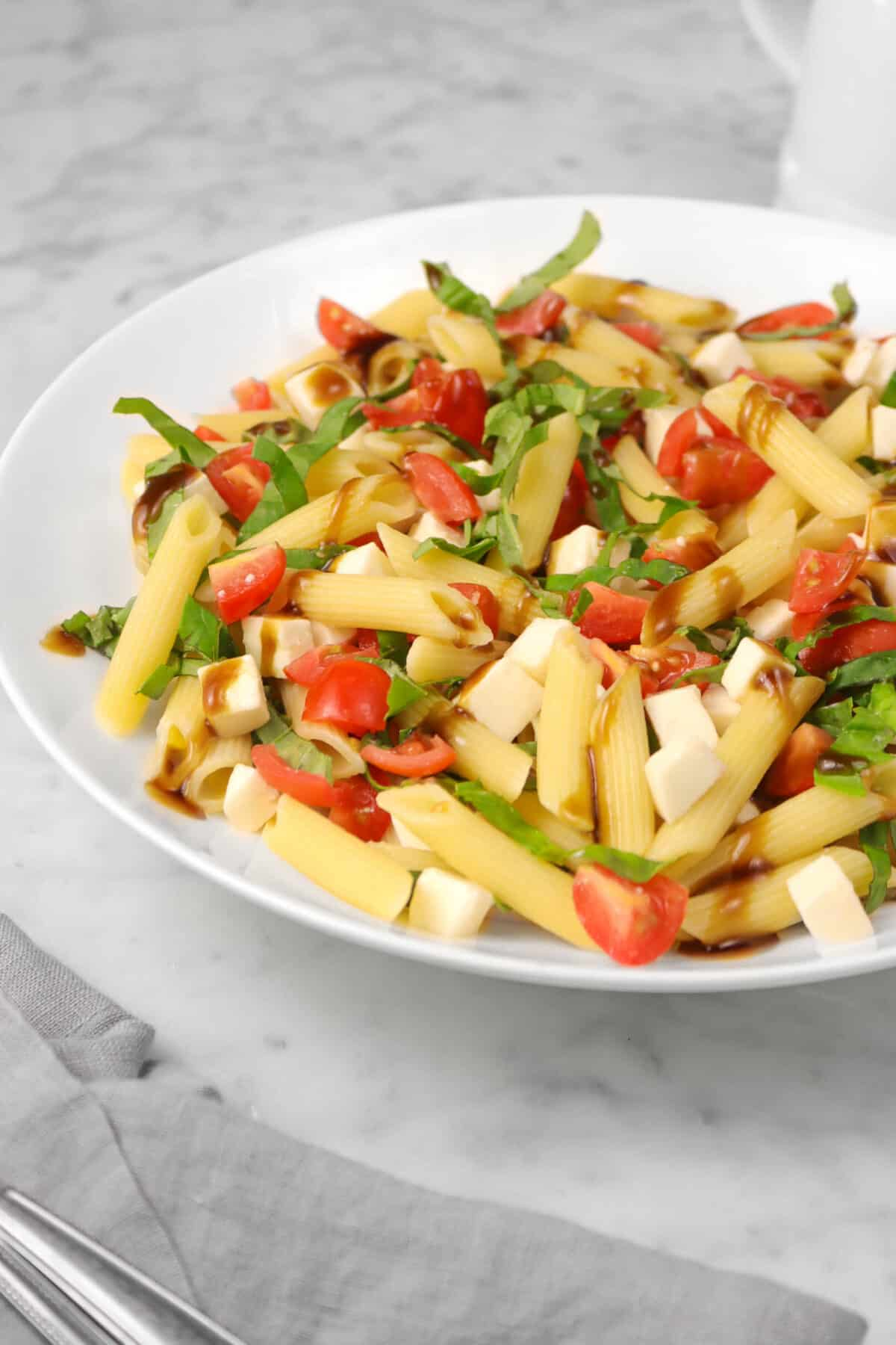 caprese pasta salad in a white bowl with a grey napkin