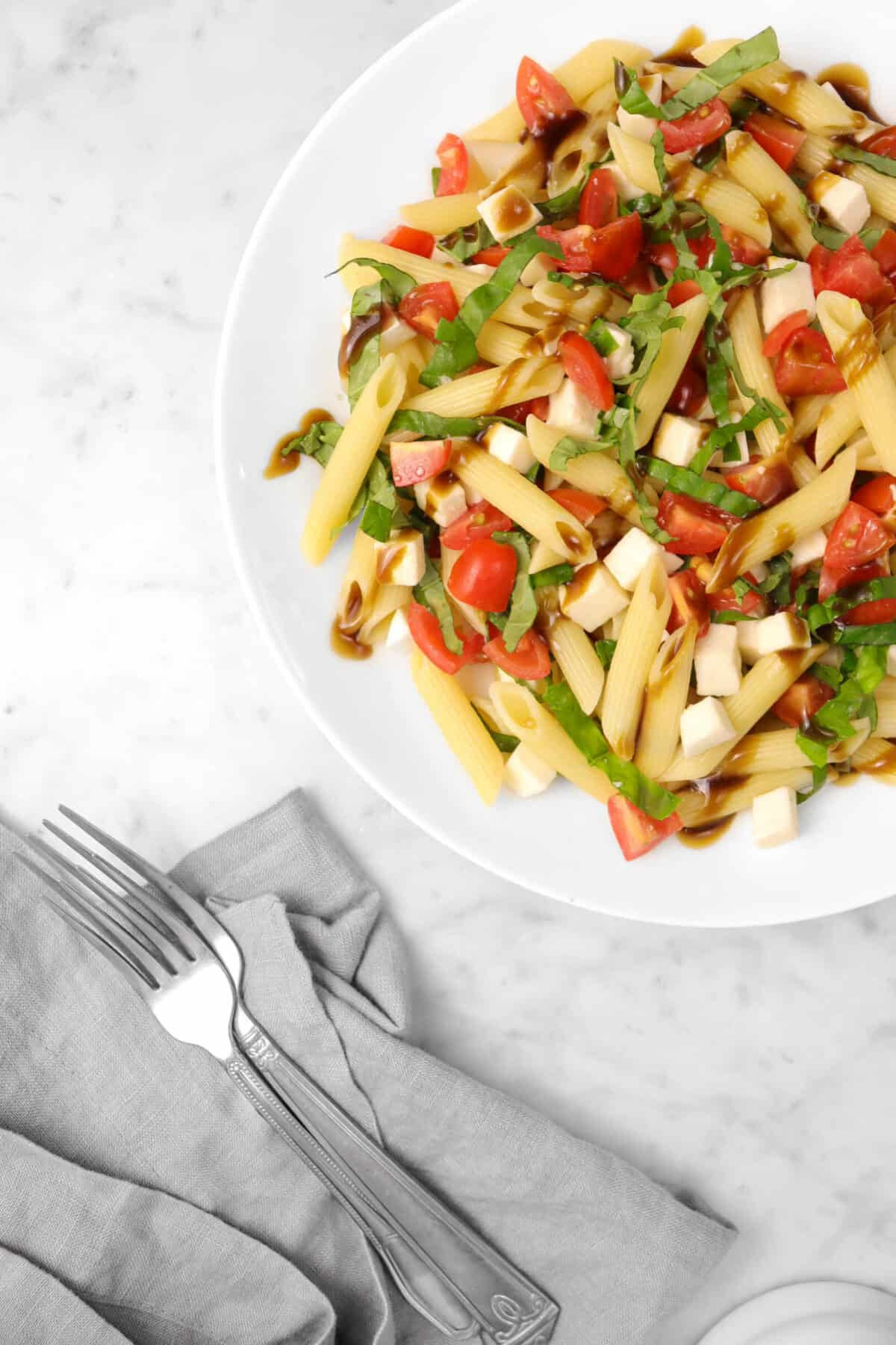 overhead shot of caprese pasta salad in a white bowl with a grey napkin and two forks