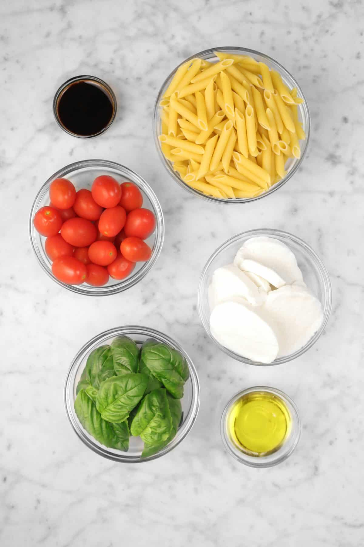 ingredients for caprese pasta salad on a marble counter