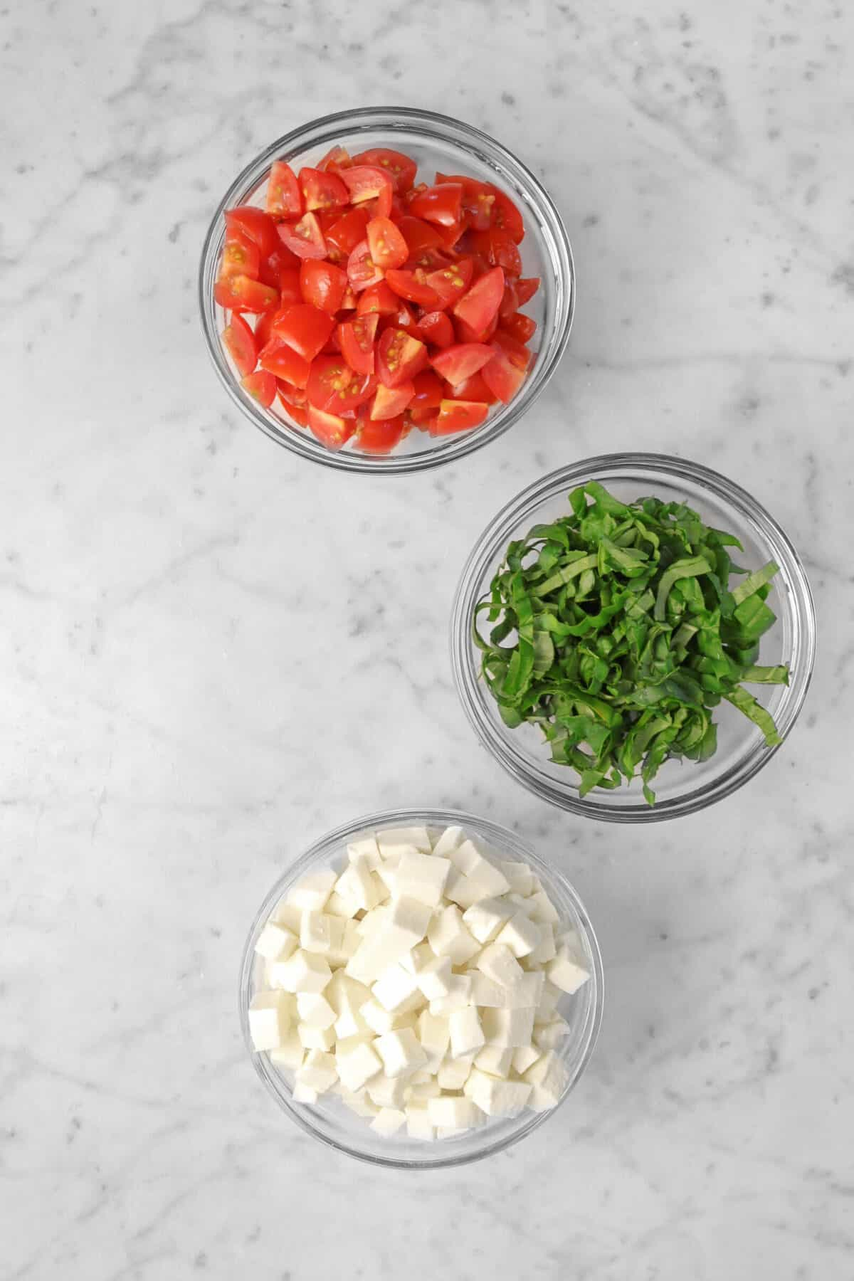 overhead shot of three small bowls filled with chopped tomatoes, chopped basil, and chopped mozzarella