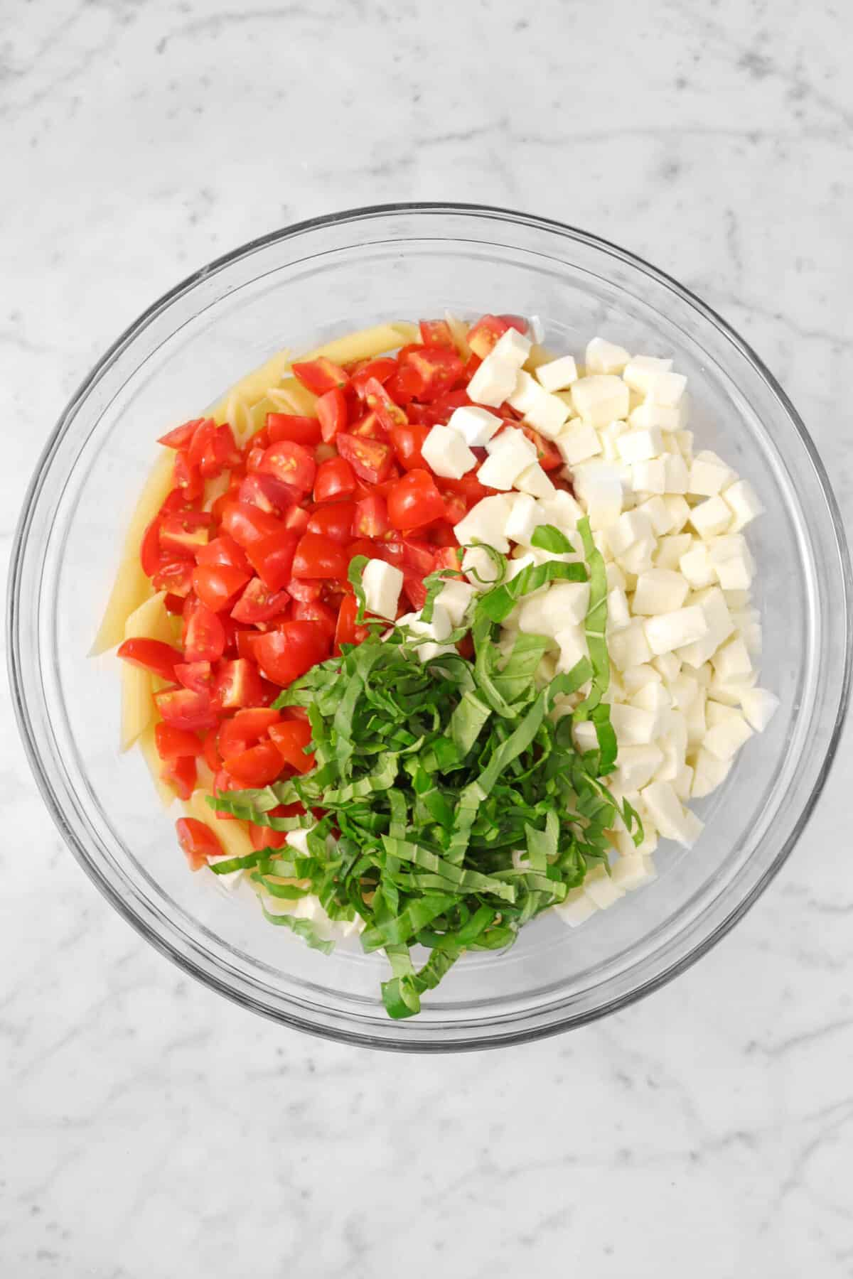 penne pasta, chopped tomatoes, chopped mozzarella cheese, and chopped basil in a large glass bowl