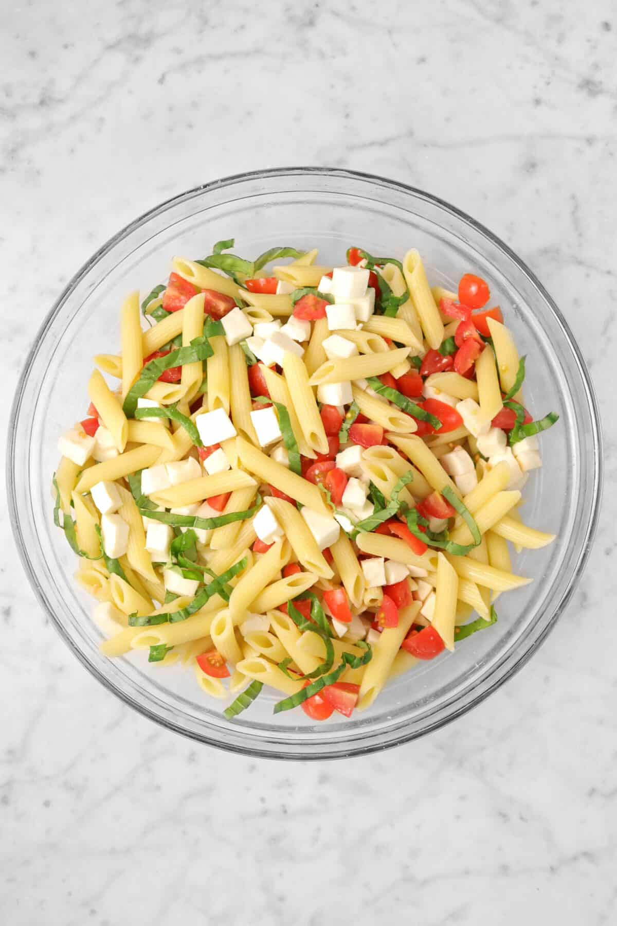 caprese pasta salad in a glass bowl on a marble counter