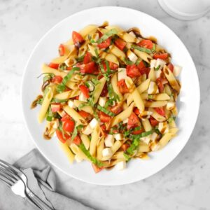 caprese pasta salad with balsamic vinaigrette dressed over the top with a grey napkin, two forks, and a white pourer with vinaigrette