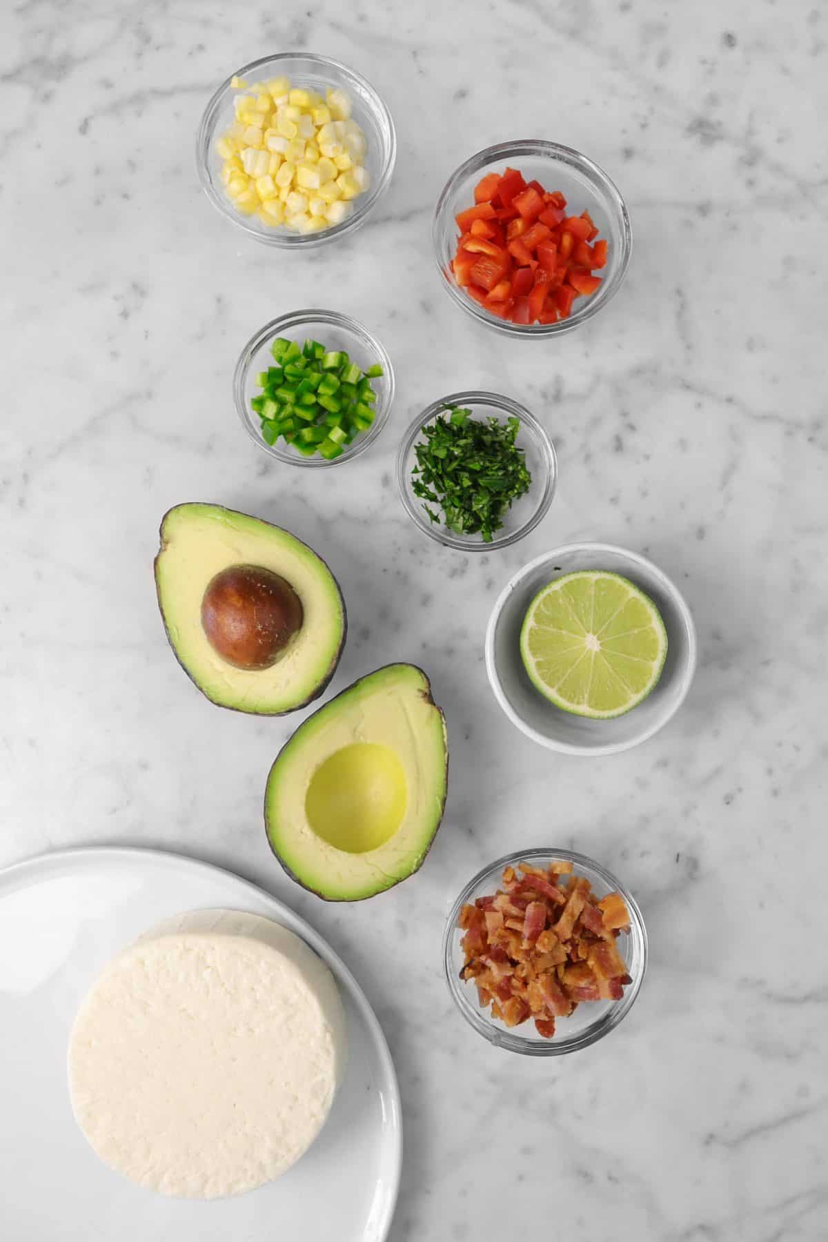 ingredients for loaded guacamole on a marble counter