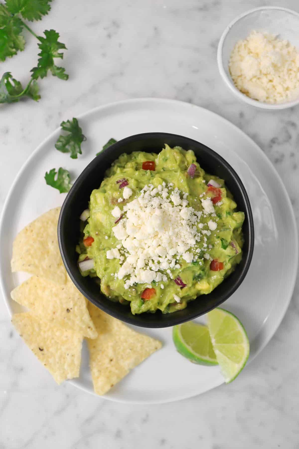 a bowl of guacamole on a white plate with chips, cilantro leaves, and slices of lime with a white bowl of crumbled cotija cheese
