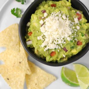 a bowl of guacamole on a white plate with chips, lime slices, and cilantro leaves