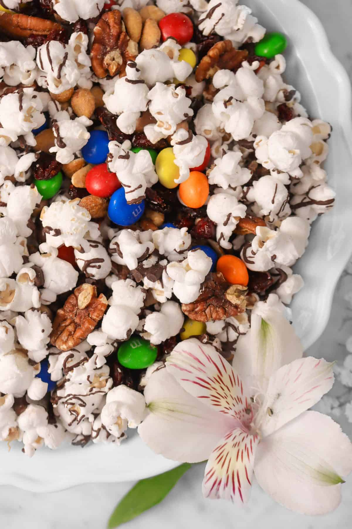 a white pie plate with popcorn mix on a marble counter with a flower