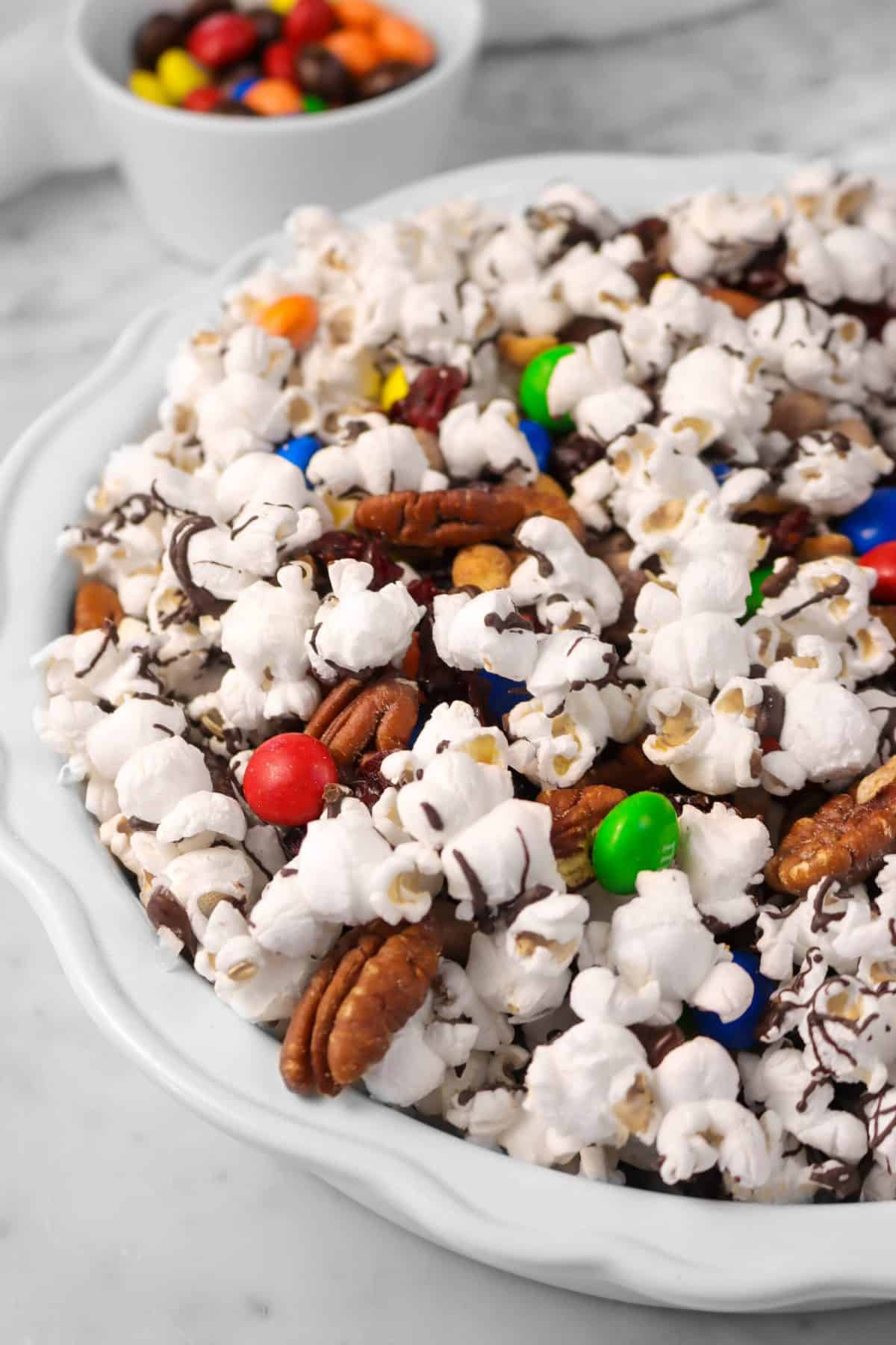 a white pie plate with popcorn mix on a marble counter with bowl of M&M's