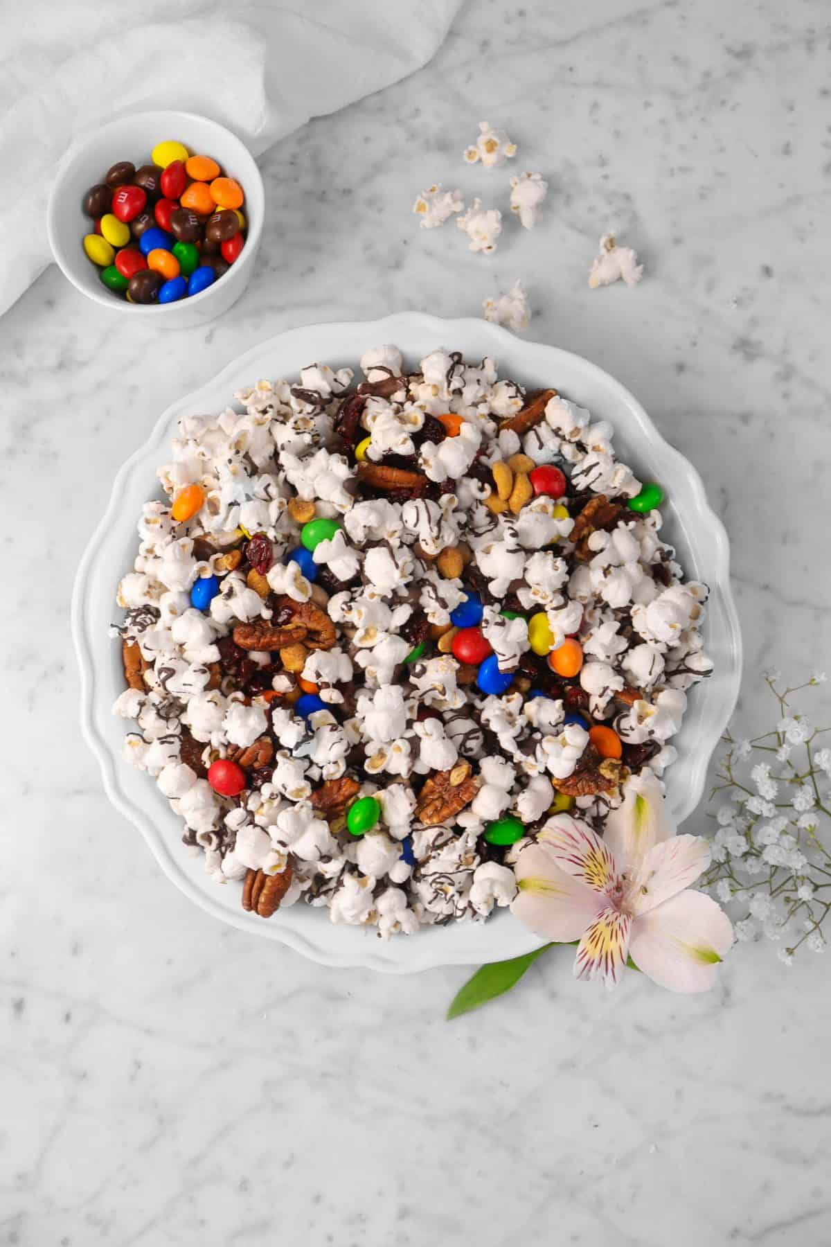 a pie plate with popcorn mix on a marble counter with fresh flowers, a bowl of M&m's, and a white napkin