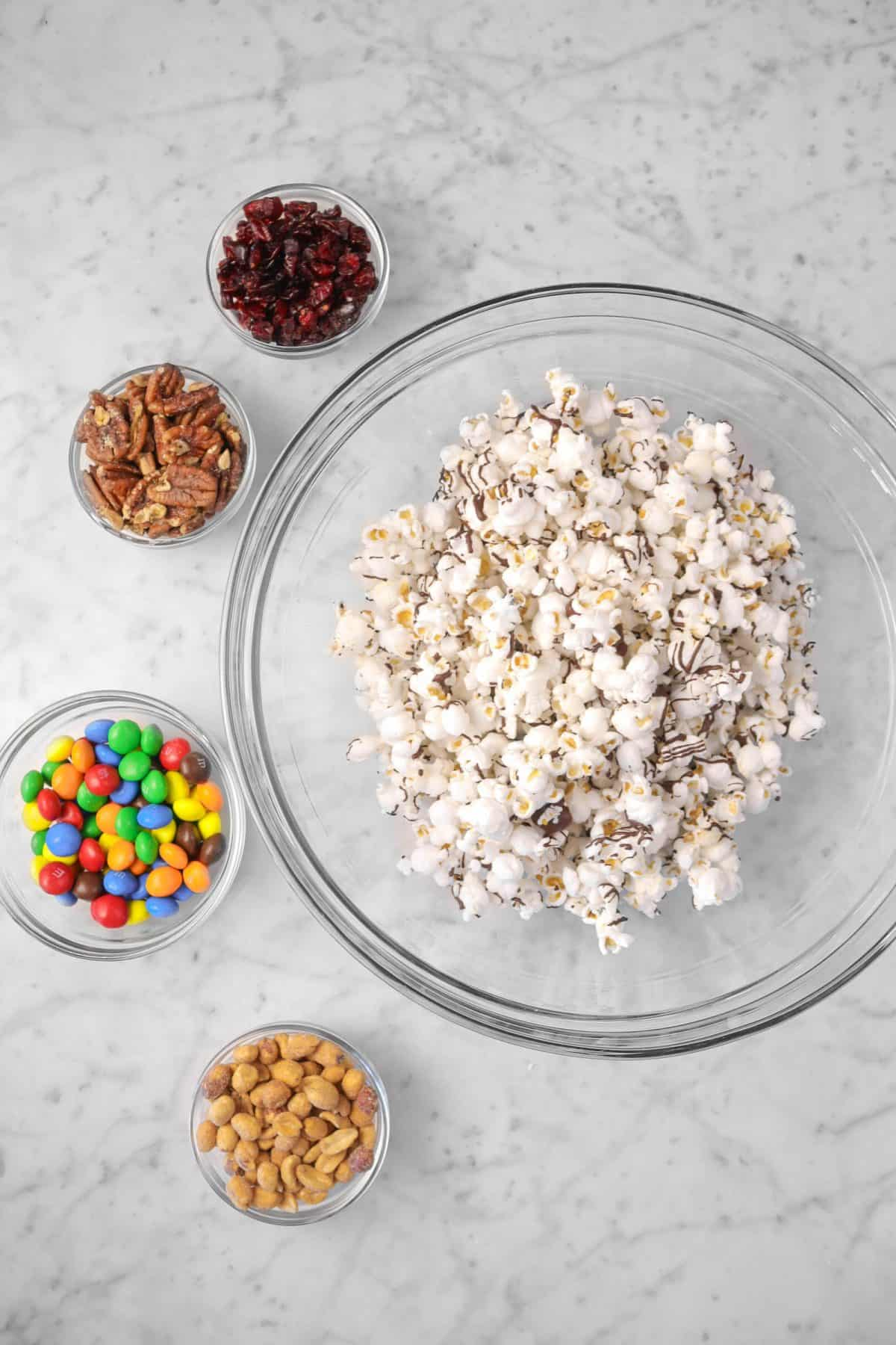 pop corn in a glass bowl with bowls of cranberries, nuts, and m&m's next to it