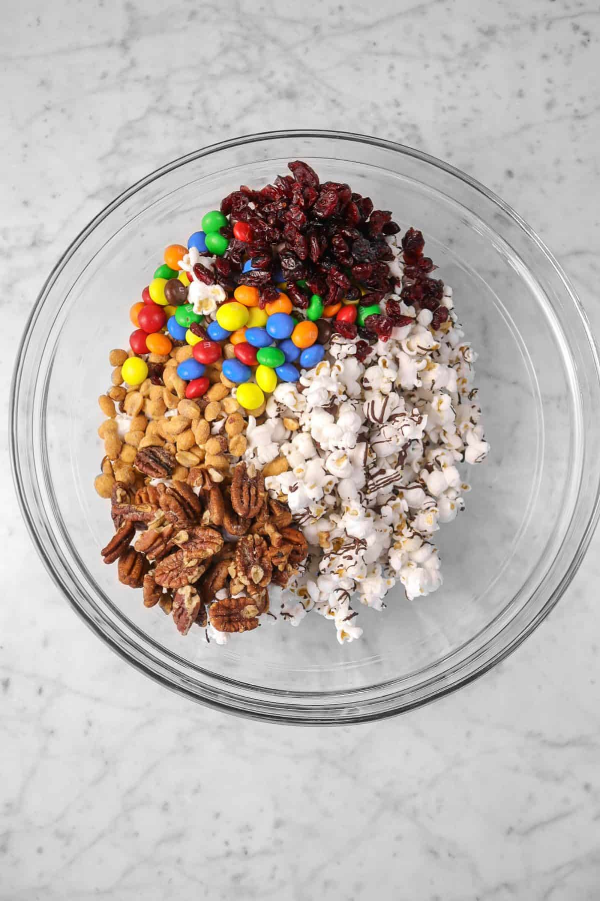popcorn, cranberries, nuts, and m&m's in a glass bowl