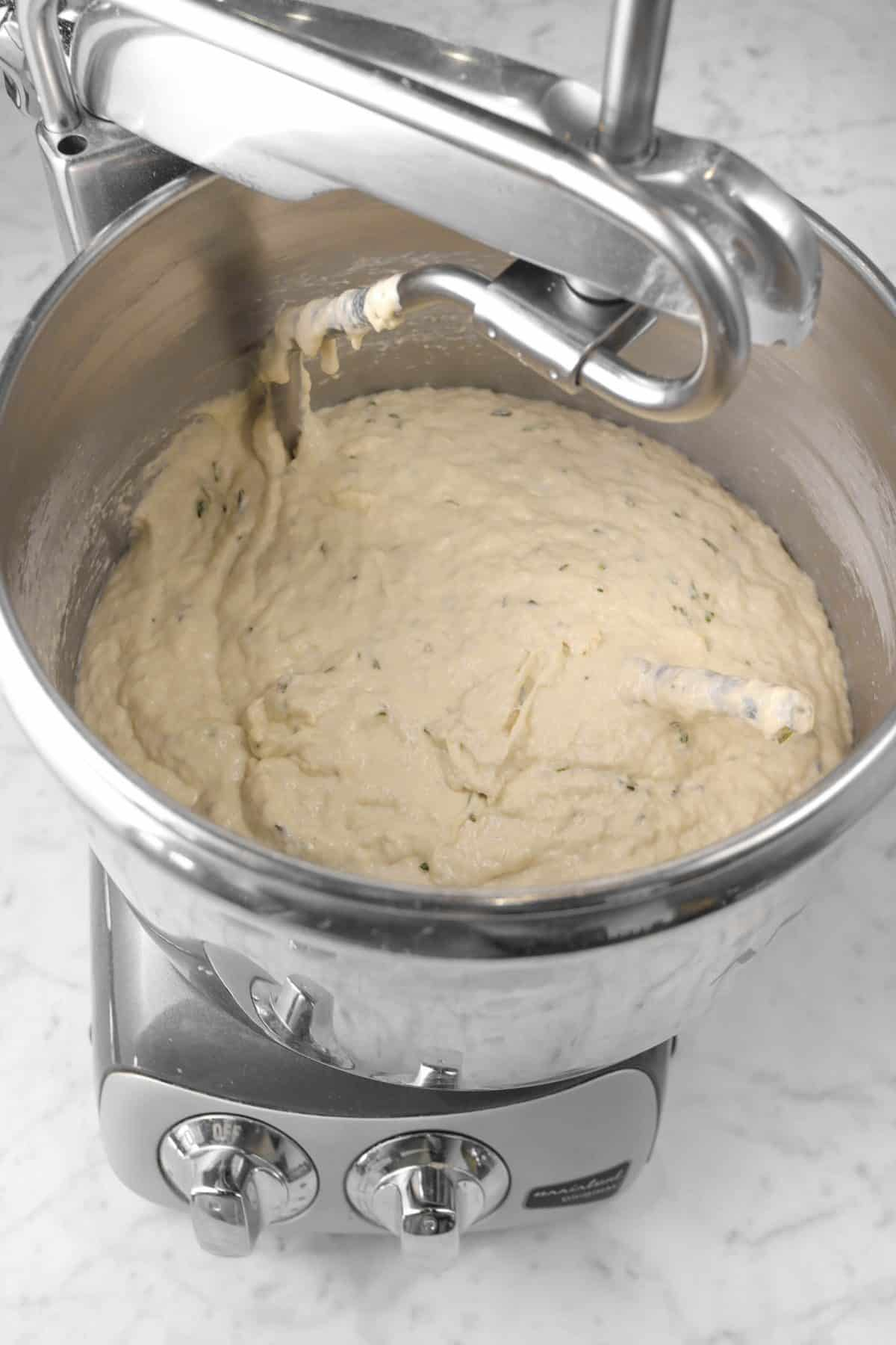 focaccia dough in a mixer after salt has been stirred in