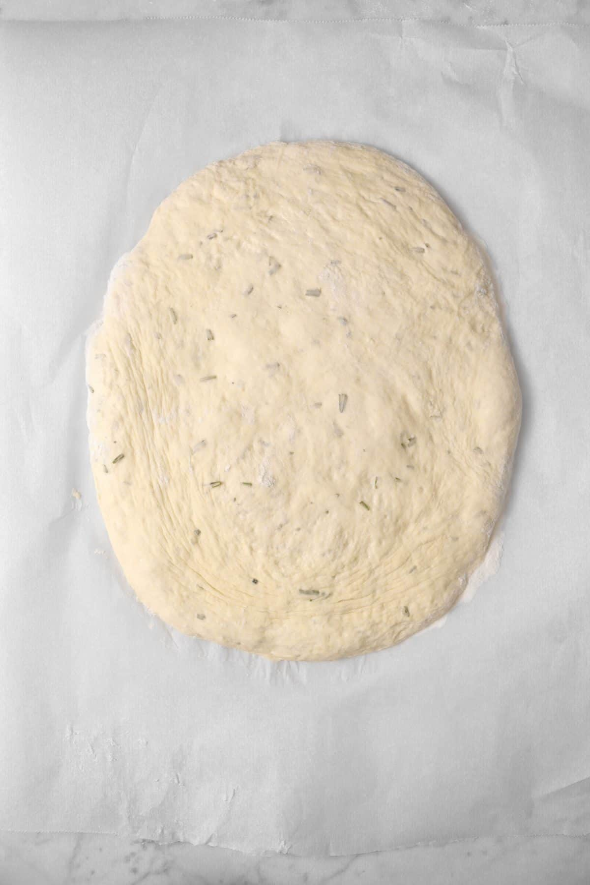 focaccia dough pressed down into a small oval on a piece of parchment