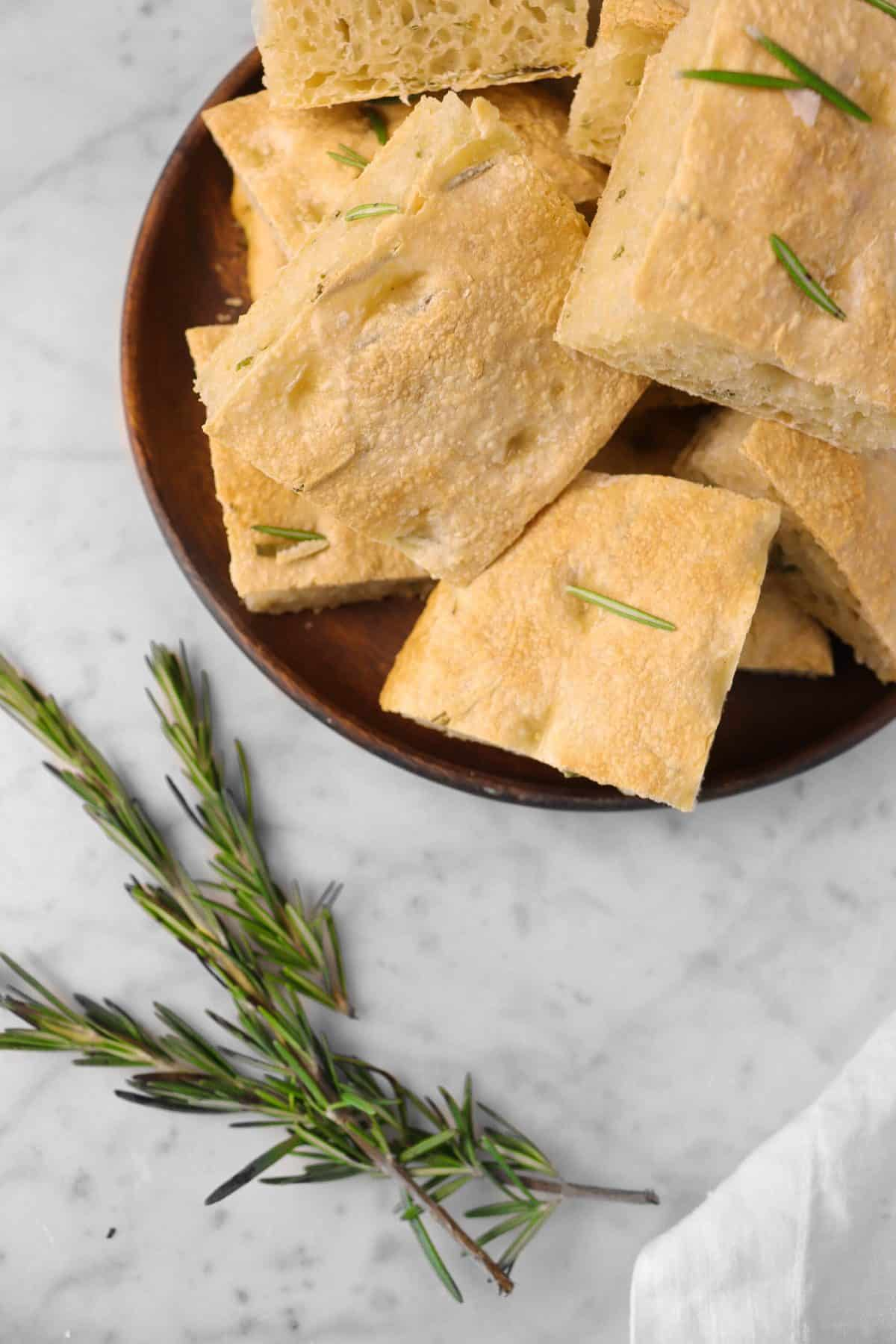sliced focaccia on a wooden plate with sprigs of fresh rosemary