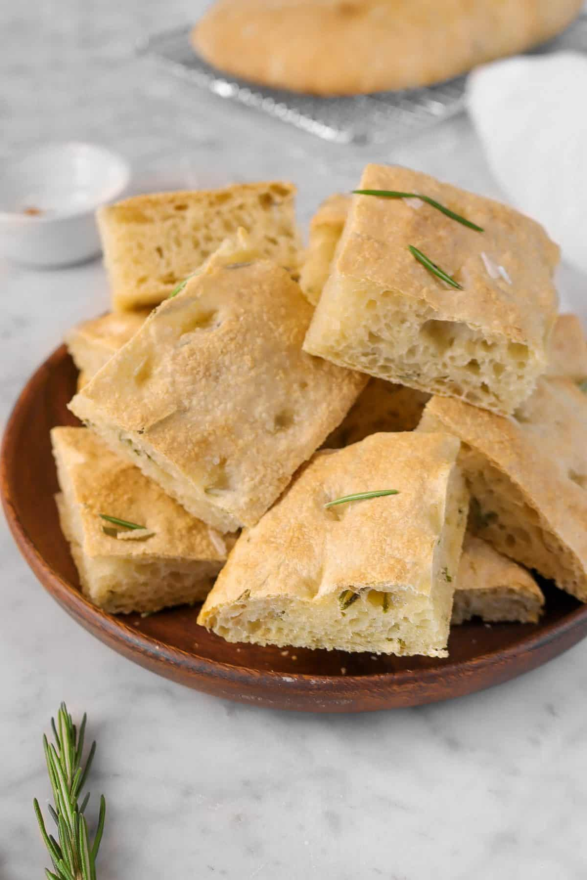sliced rosemary focaccia on a wooden plate with a loaf of focaccia in the background