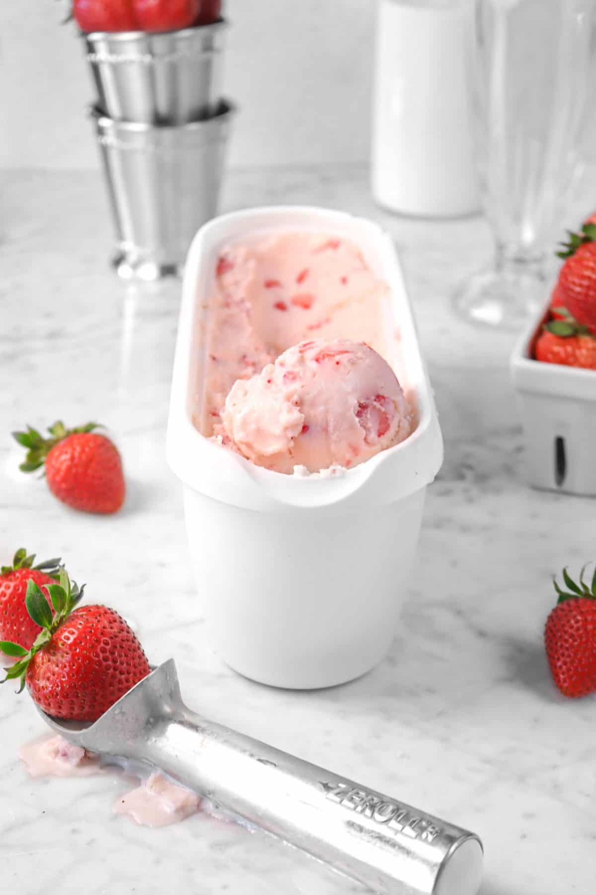 strawberry ice cream in a white container with strawberries, an ice cream scoop, and stainless steel mint julep cups in the background