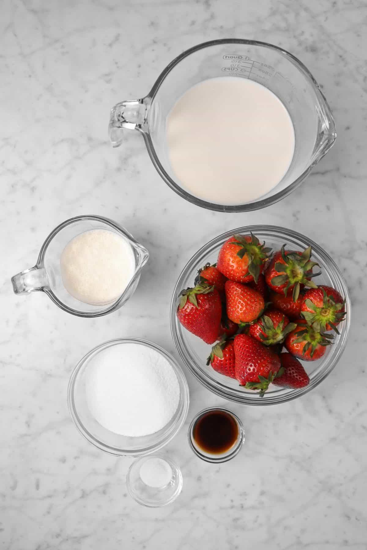 ingredients for strawberry ice cream on a marble counter