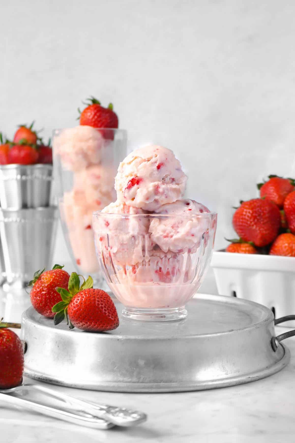 four scoops of strawberry ice cream in a glass bowl on a stainless steel baking pan with fresh strawberries and a milk shake glass with four scoops of strawberry ice cream in the background