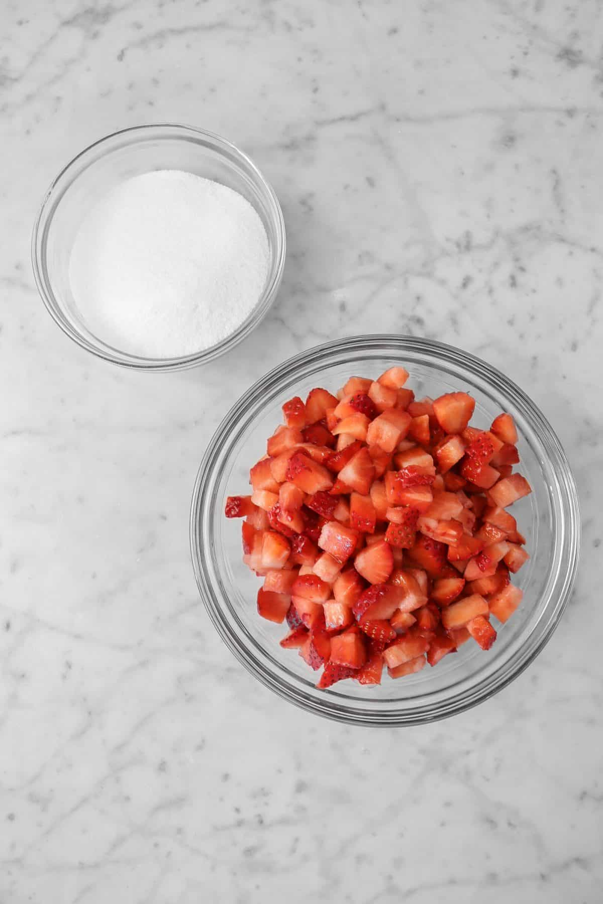 chopped strawberries in a glass bowl with a bowl of sugar on a marble counter