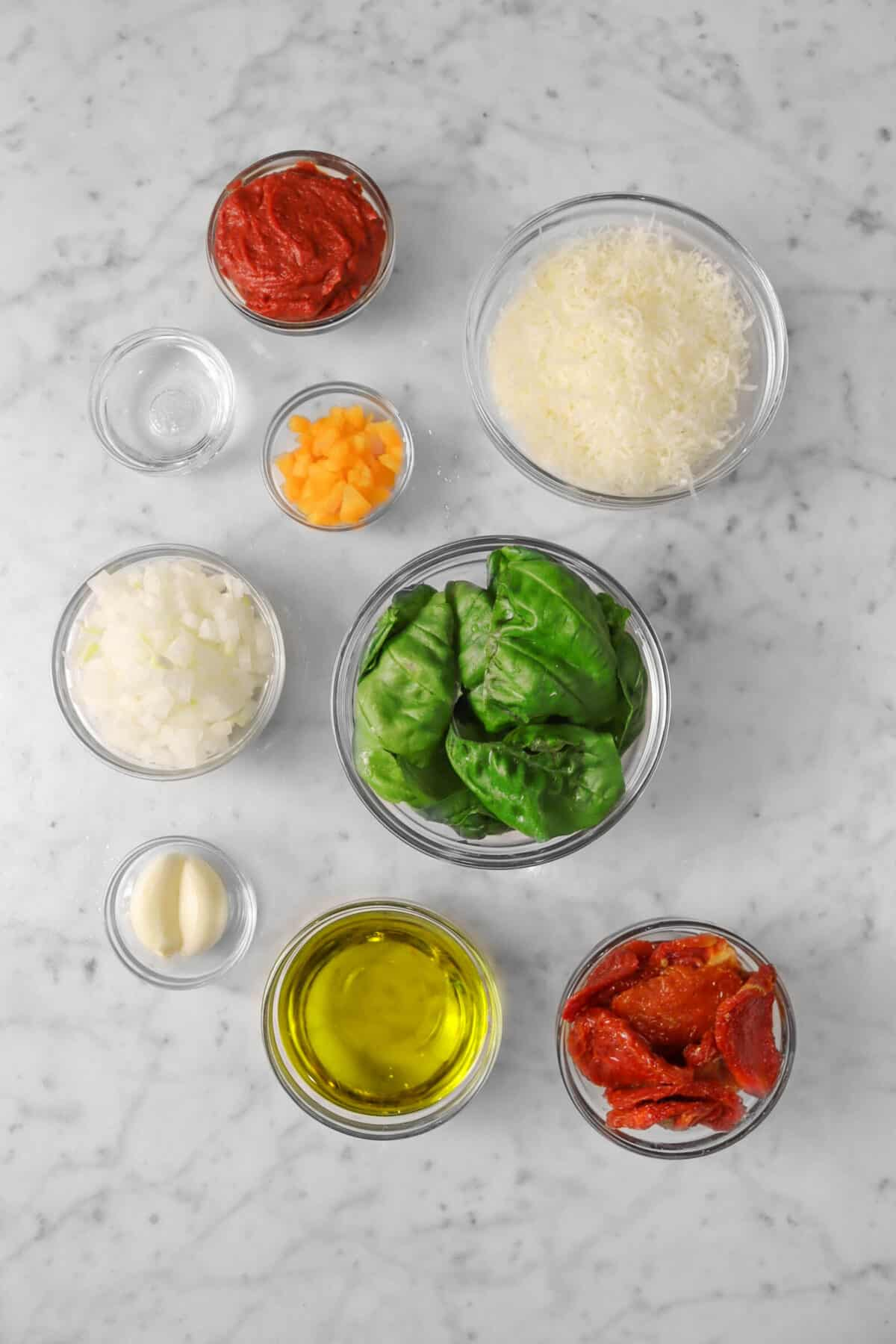 ingredients for tomato pesto on a marble counter