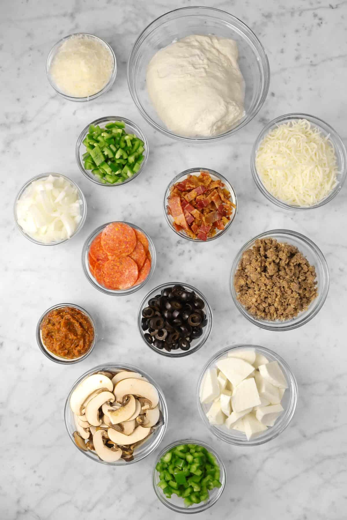 ingredients for supreme pizza on a marble counter