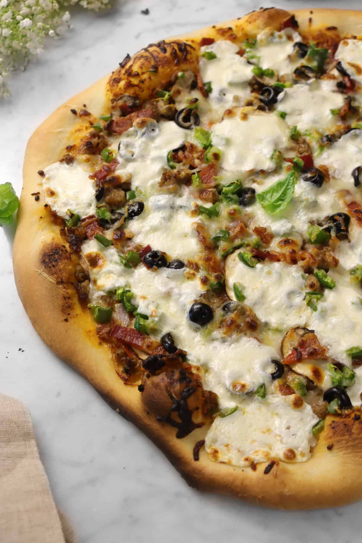 supreme pizza on a marble counter with basil leaves and white flowers