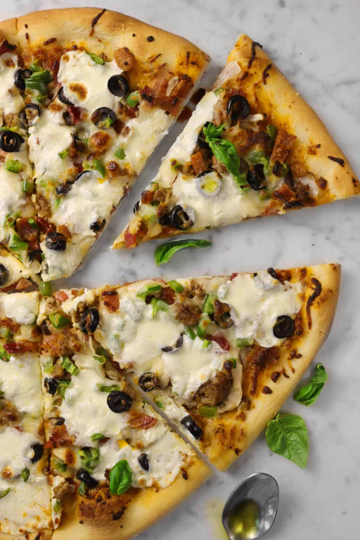 over head shot of supreme pizza with only four pieces showing, one of which is pulled away on a marble counter with four basil leaves and a silver spoon