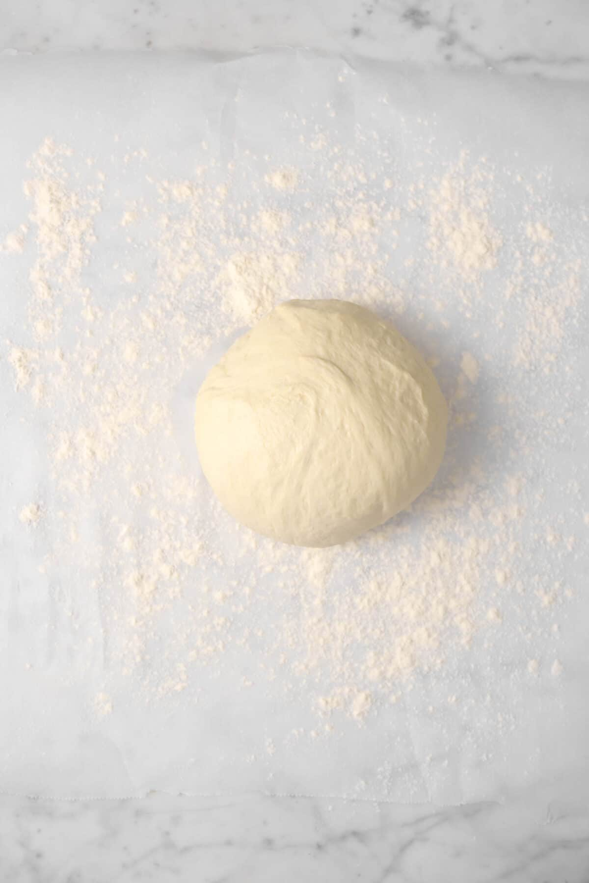 pizza dough on a piece of floured parchment paper