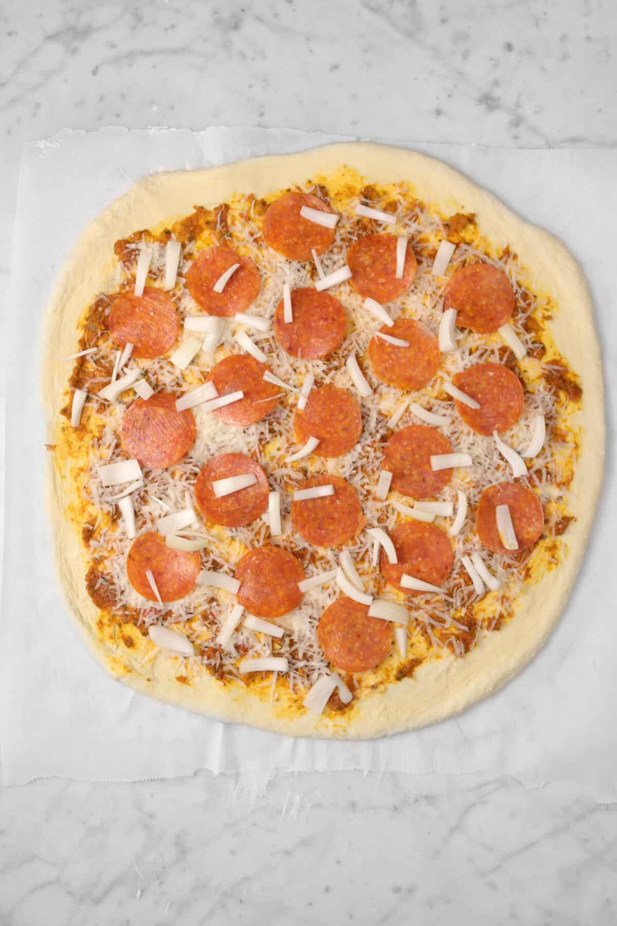 sliced yellow onions added on top of pepperoni layer on pizza dough