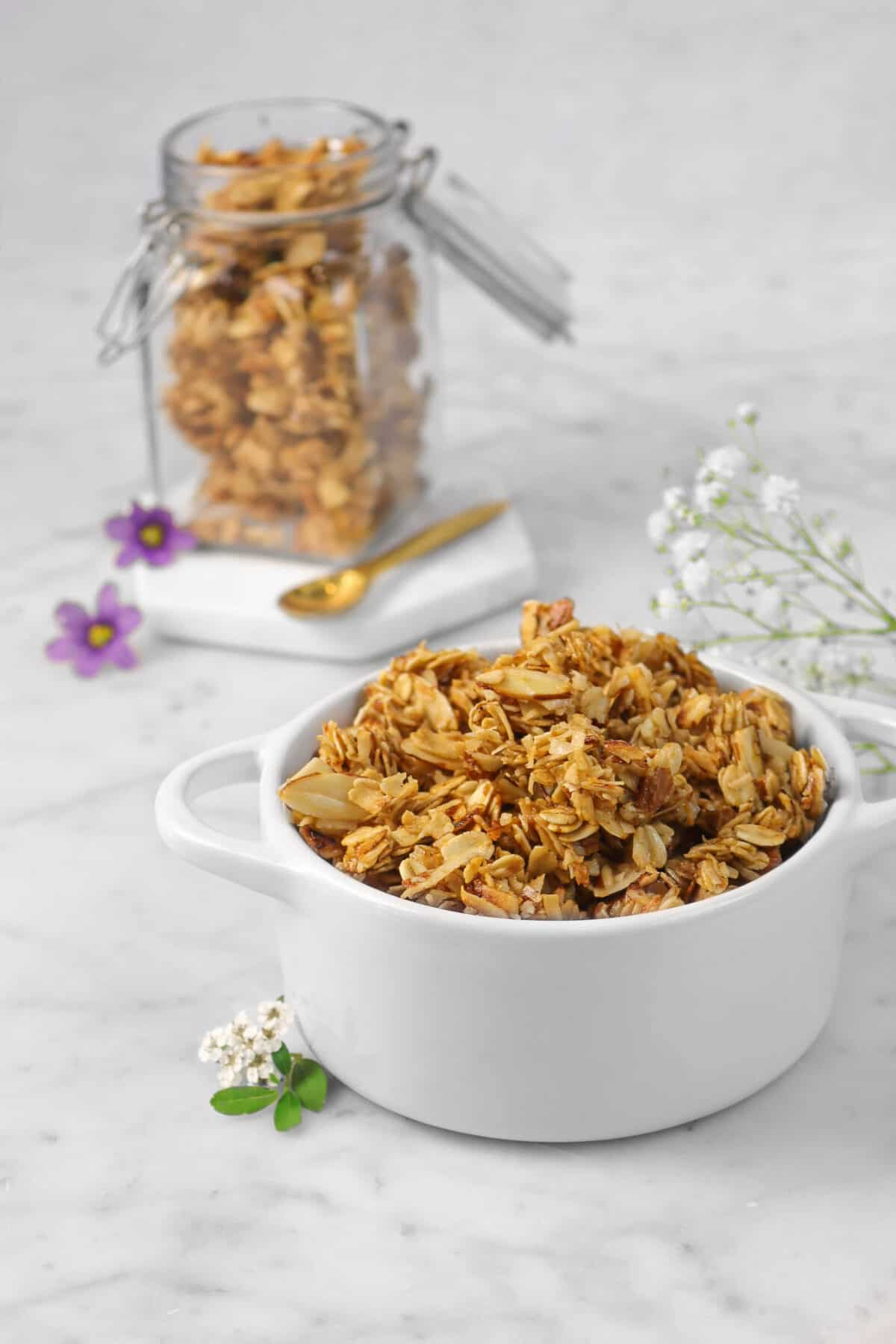 granola in a small white cocotte with fresh flowers, a gold spoon, and a jar of granola