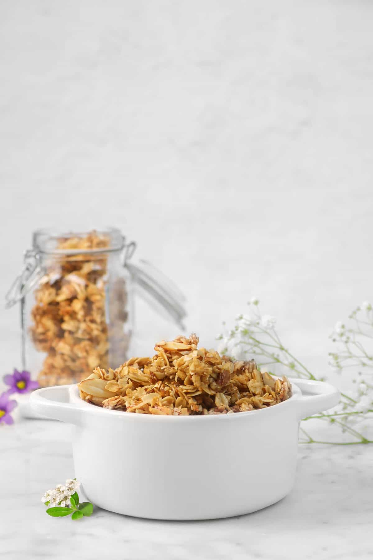 granola in a white cocotte with fresh flowers and a jar of granola