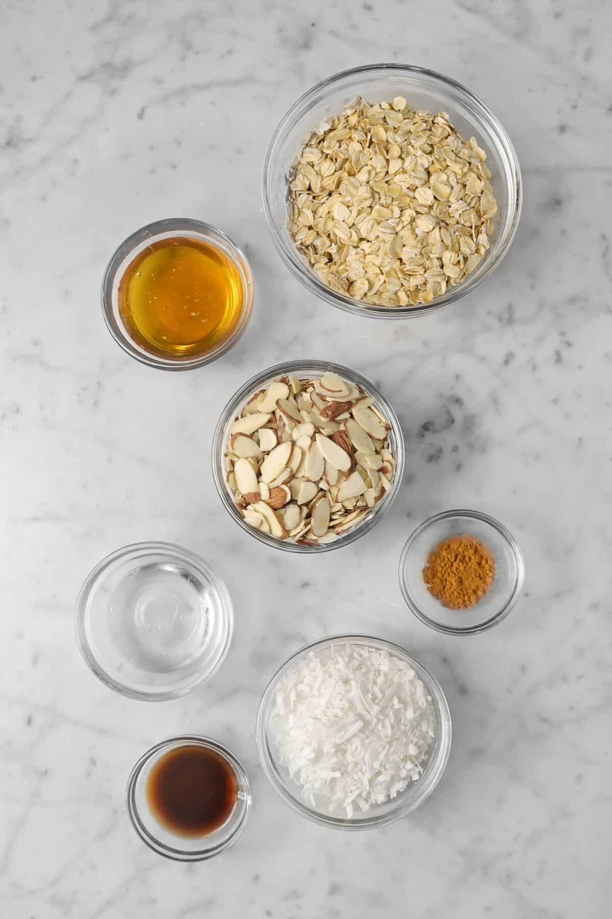 oatmeal, honey, almonds, cinnamon, coconut, vanilla, and coconut oil in glass bowls