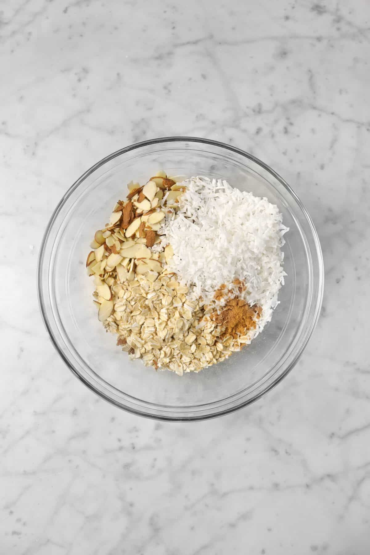 oatmeal, slivered almonds, shredded coconut, and cinnamon in a glass bowl