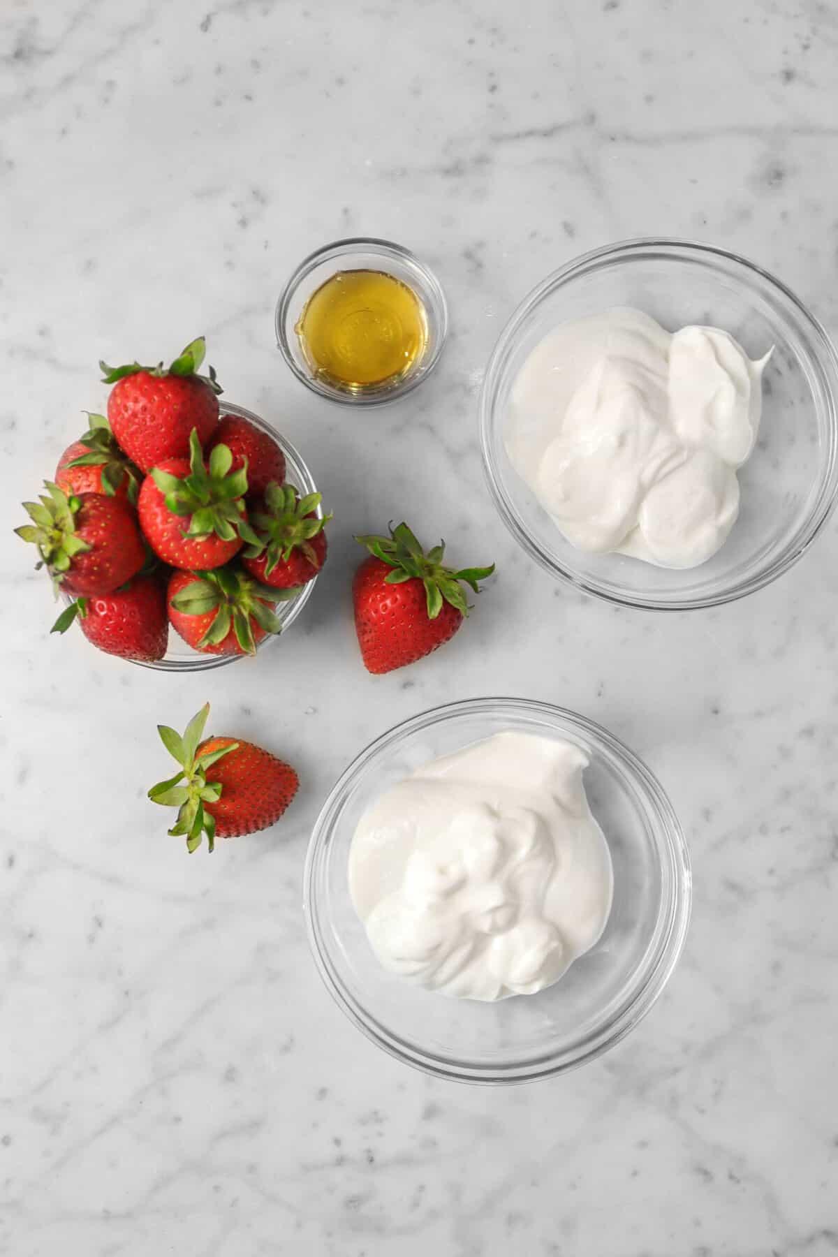yogurt, strawberries, and honey in glass bowls