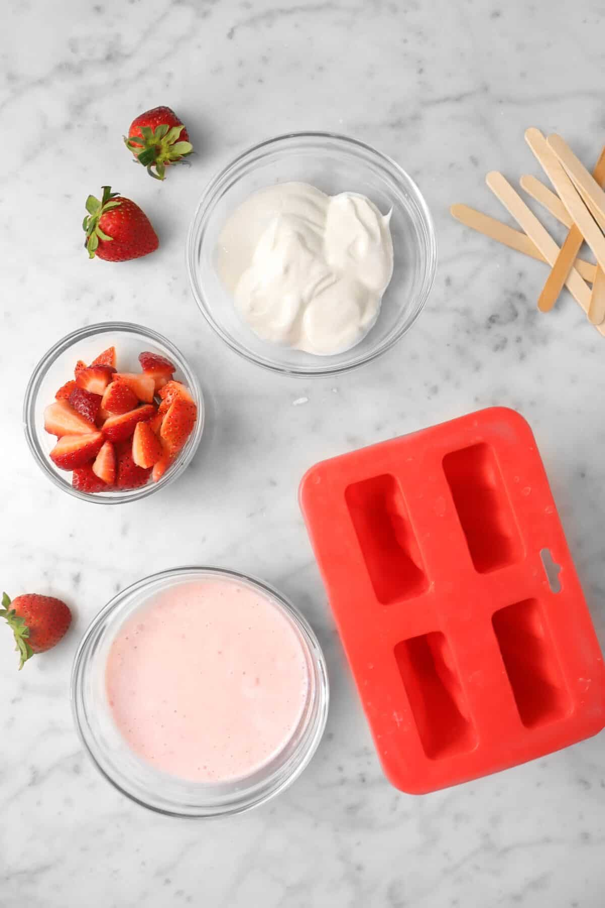 yogurt, chopped strawberries, and strawberry yogurt in glass bowls with popsicle mold