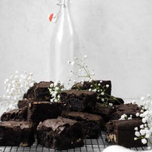 blackout brownies on a wire cooling rack with white flowers, a napkin, and a milk bottle