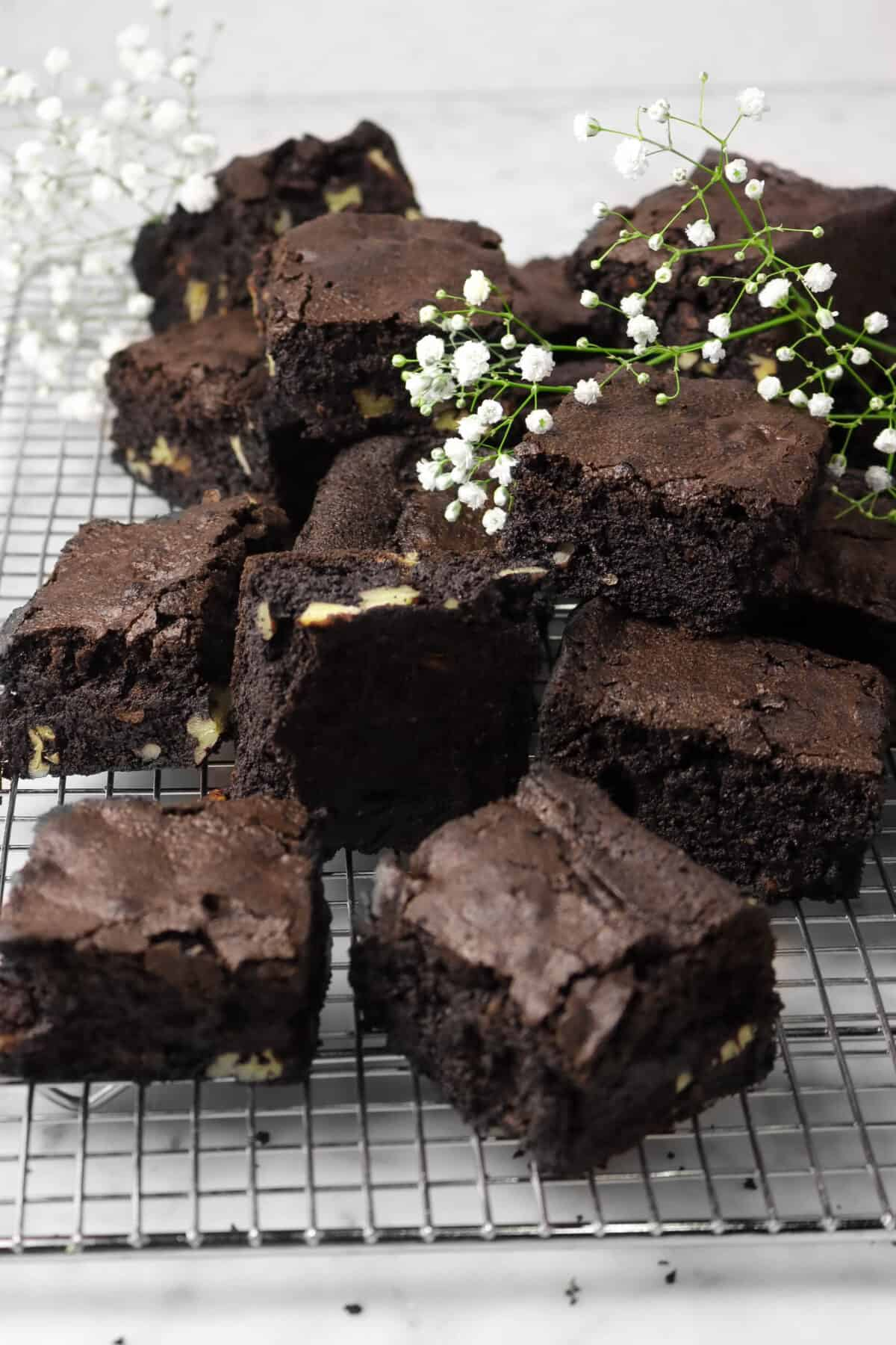 blackout brownies stacked on a wire cooling tack with white flowers