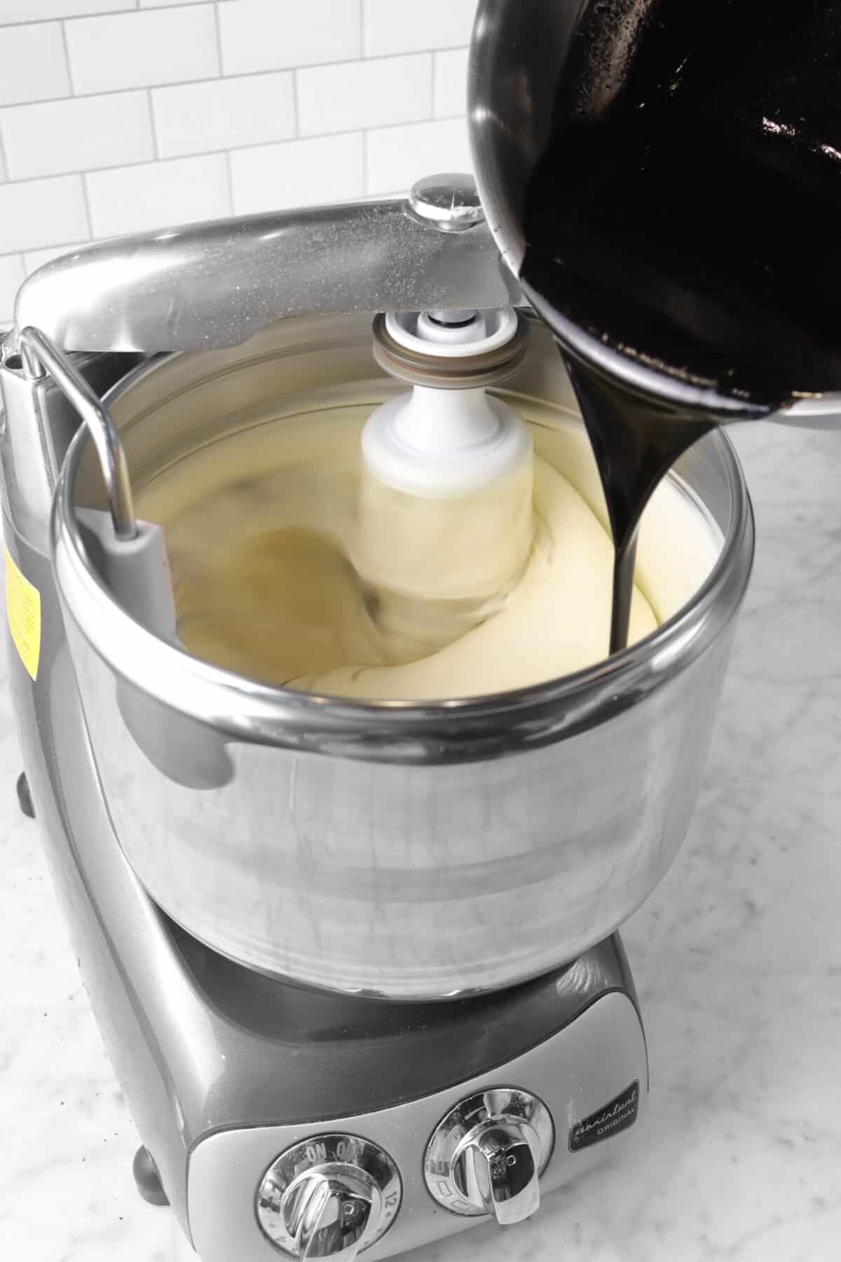 cocoa and butter mixture being poured into egg mixture