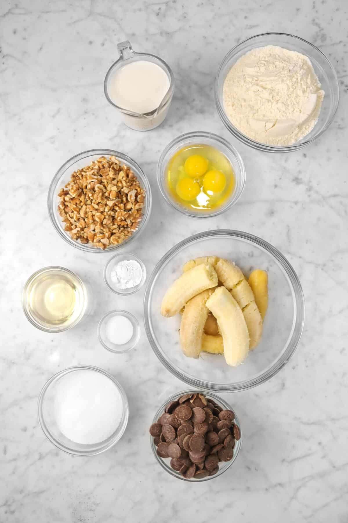 flour, eggs, bananas, chocolate, sugar, salt, baking powder, oil, walnuts, and milk in glass bowls
