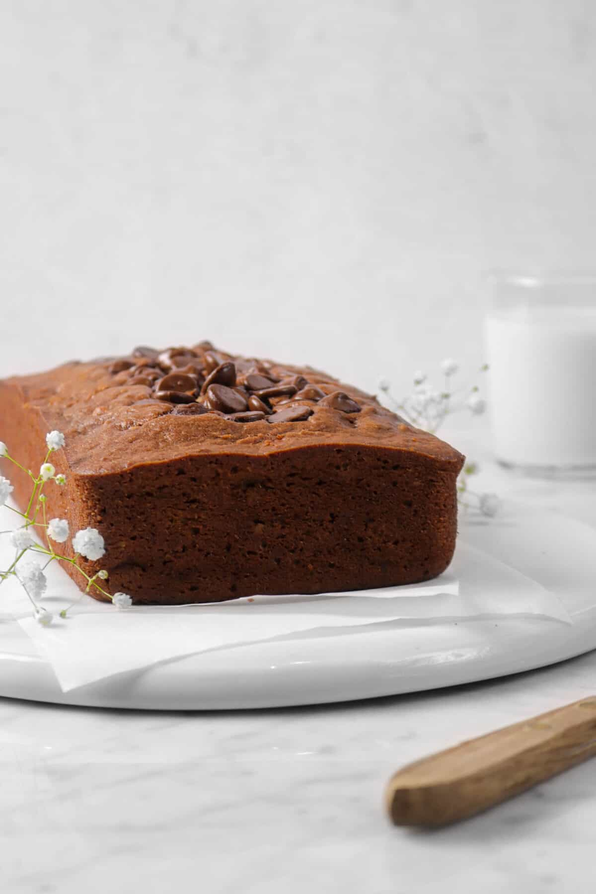 chocolate banana bread on a white plate with parchment, white flowers, glass of milk, and a wood knife