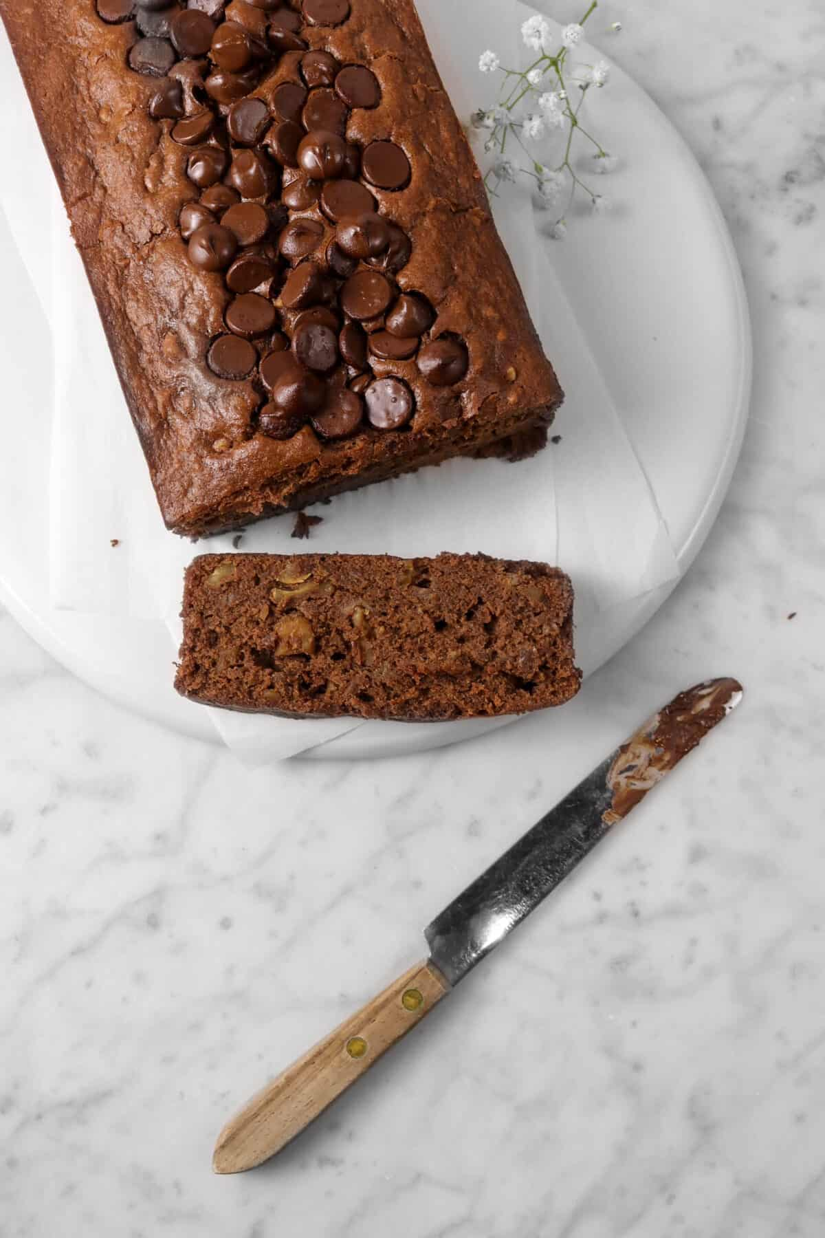 overheat shot of chocolate banana bread with chocolate covered knife and white flowers