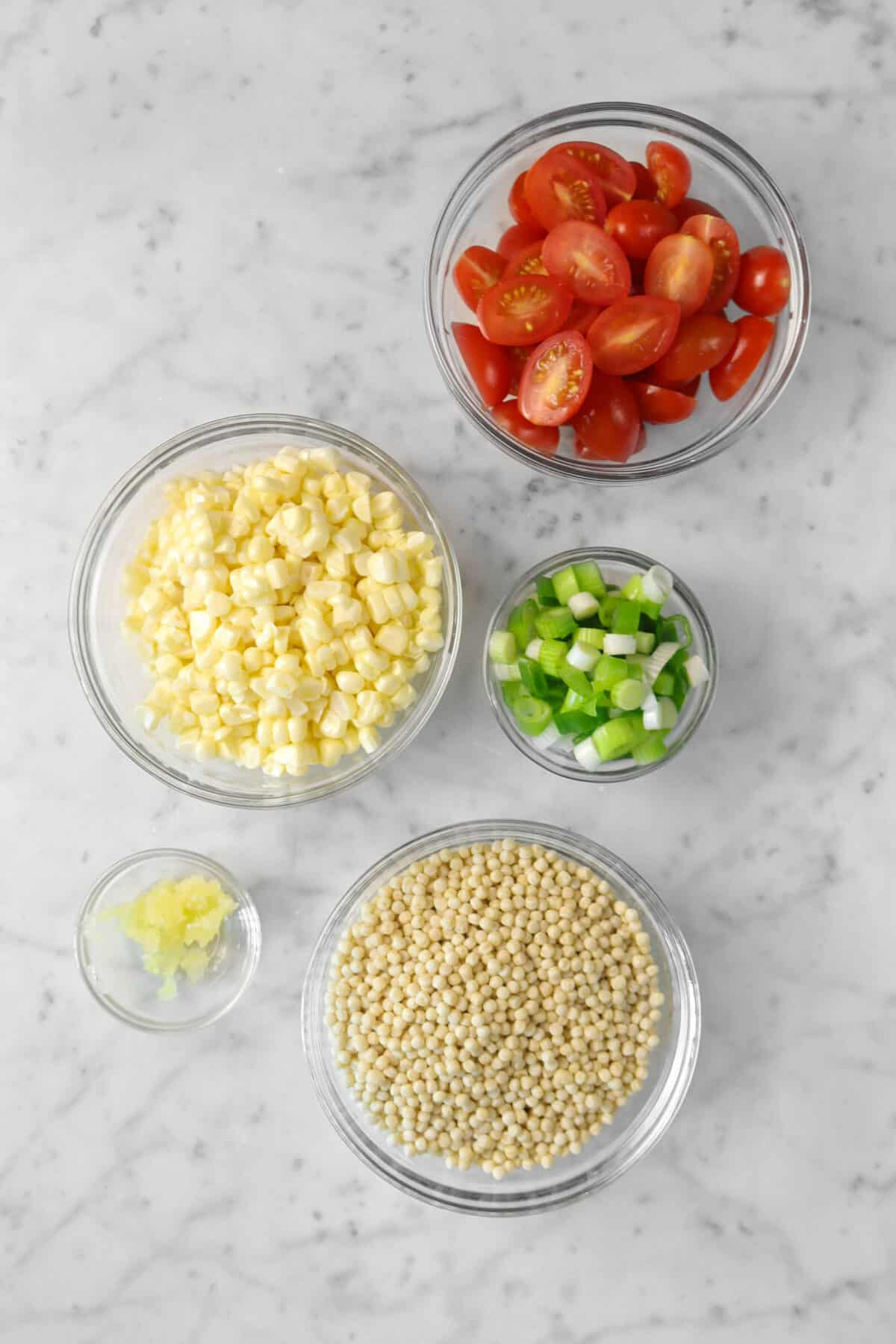 sliced tomatoes, corn, green onions, garlic, and couscous in small bowls